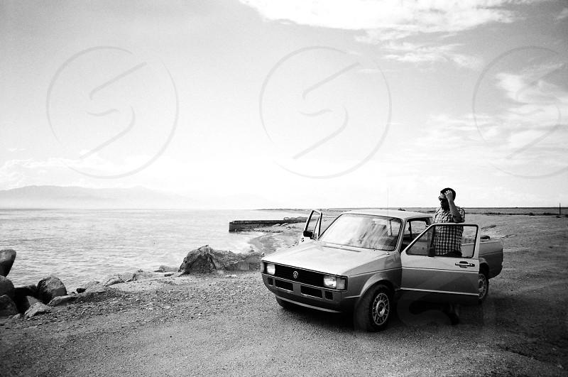 man standing beside gray 2 door truck beside sea shore photo