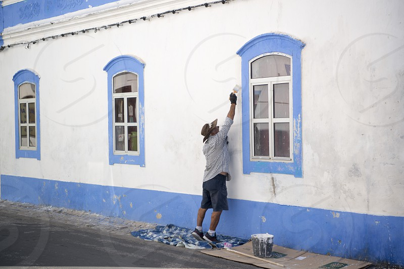 a men painting his house in the Town of Cabanas near Tavira at the east Algarve in the south of Portugal in Europe. photo