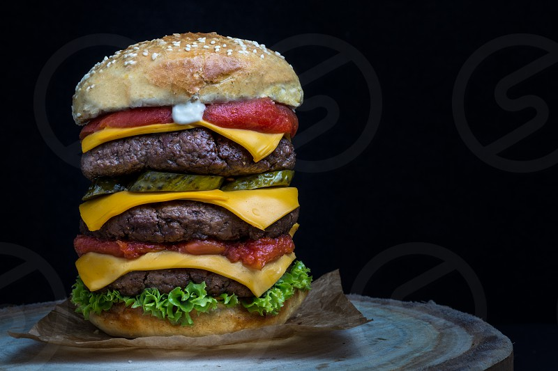 Triple cheeseburger with tomato lettuce pickles and mayonnaise on a wooden table photo