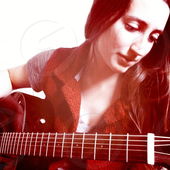 woman holding black acoustic guitar photo