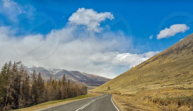 Straight road goes to horizon on mountains backdrop. Altay mountains Siberia Russia. photo