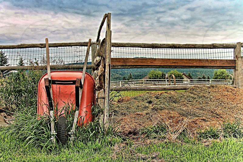 A red wheelbarrow balances on its wheel against a farm fence photo