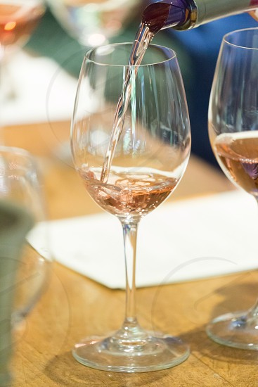 A glass of rose wine being poured  photo