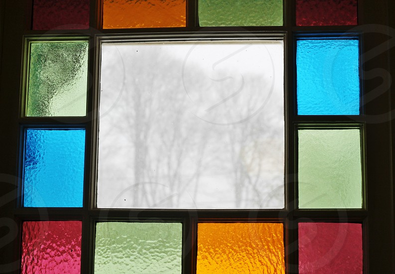Snow and trees through stained glass window  photo