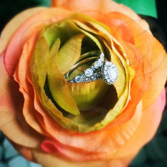 diamond silver ring in a orange plastic flower photo