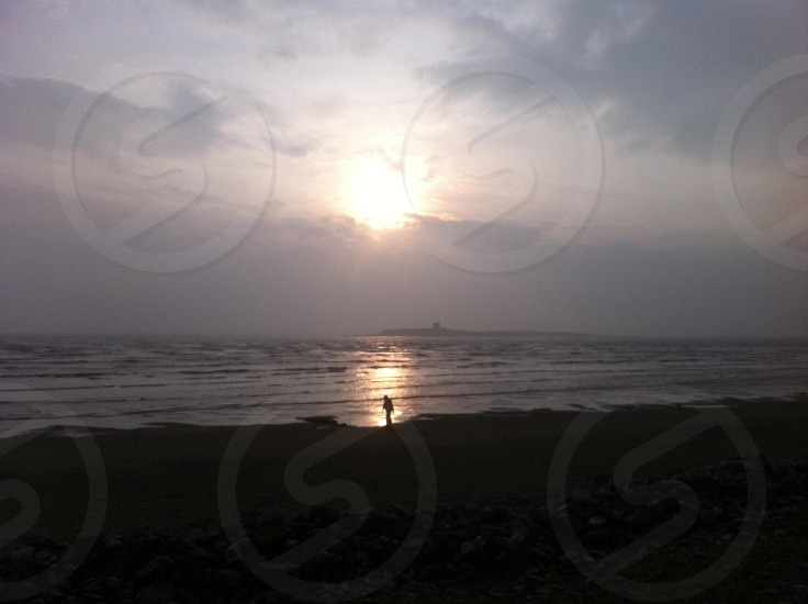 Sunrise on a beach with an early morning walker. photo