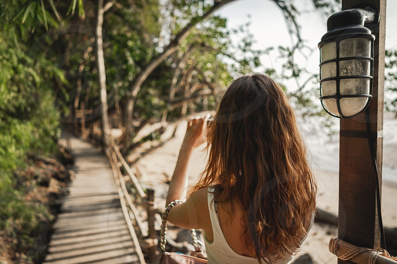Woman takes photo on smartphone of wooden pathway Monkey Trail to Pai Plong Centara beach in Ao Nang in Krabi in Thailand. Back view photo