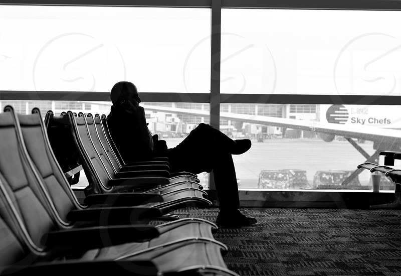 A traveler talks on the phone while awaiting his flight.  photo