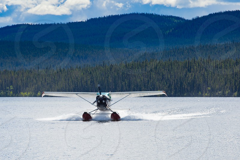 Float plane landing on remote wilderness lake in boreal forest taiga of Yukon Territory Canada photo