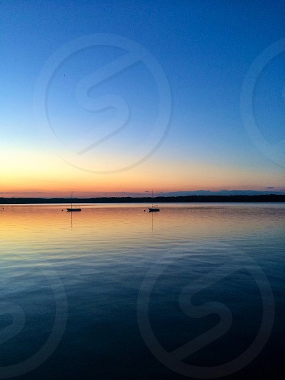 two sail-less boats on dark blue water beneath beige blue twilight sky photo