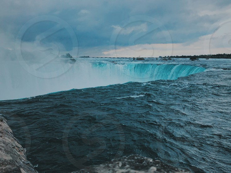 Niagara Falls modern art landscape beautiful wonderful cool water boat mist fog awesome mighty cliff waterfall Canada buffalo New York river lake blue rocks contrast nature birds hornblower maid of the mist sky clouds rushing water danger large rain clouds weather gorgeous film photo