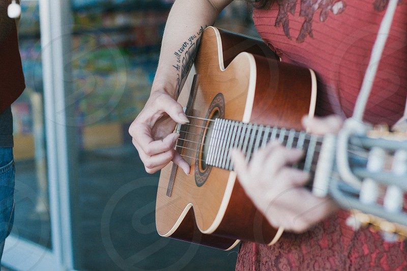 man in red printed shirt playing brown wooden acoustic guitar photo