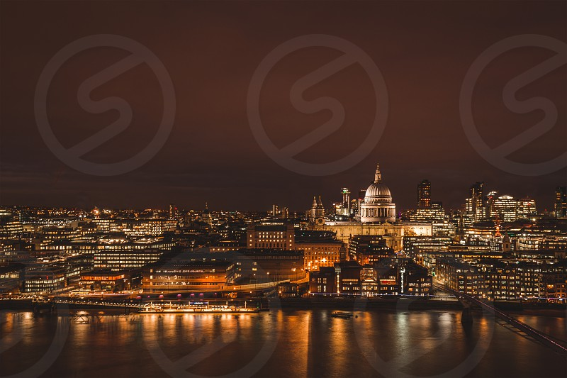 London aerial view of modern city skyline at night on the River Thames photo