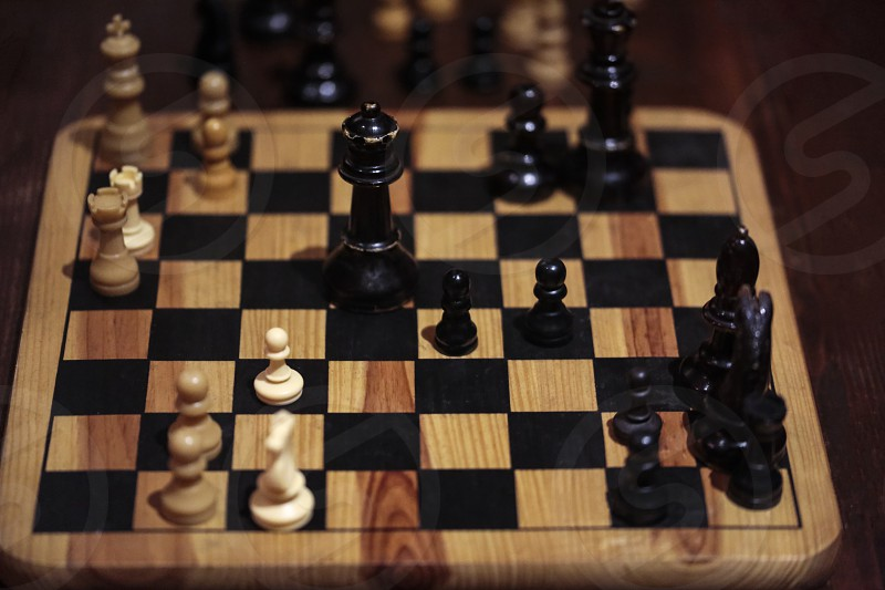 Wooden chessboard with checkers in play photo
