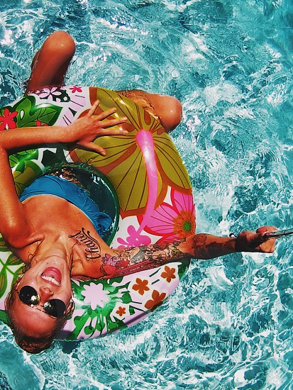 woman talking selfie using monopod while enjoying float using white green pink and beige floral print round inflatable swimming ring on clear blue water during daytime photo