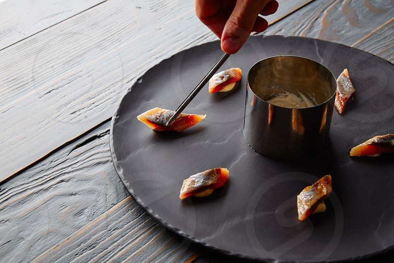 Bota sardine preparation with chef hand on black slate dish photo