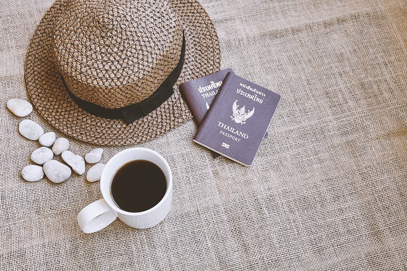 Travel concept Close up dark brown weave hat with Thai citizen passport and a white cup of black coffee on sackcloth background with copy space or empty space for text photo