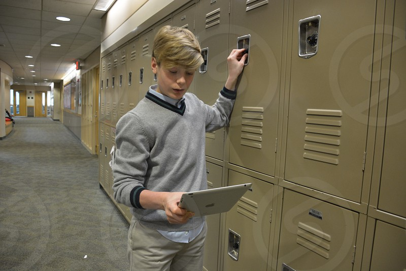 man holding ipad standing near lockers photo