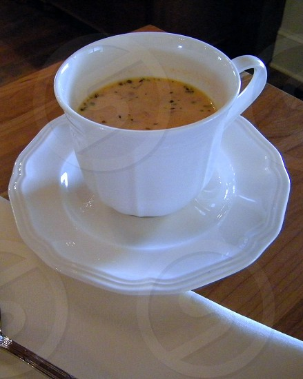 Tomato bisque in delicate white teacup with saucer photo