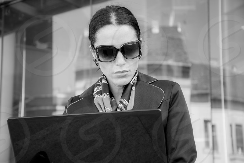 Woman working on her laptop in outdoor wearing sunglasses and having serious facemonochrome photo. photo