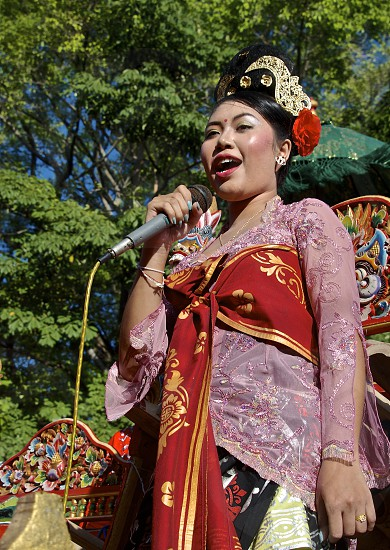 Bali parade music colorful costumes feet bells fancy fabric happy singing red pretty girl up-do. photo