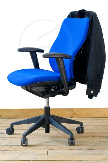 modern blue office chair on wood floor over white background with jacket on back photo