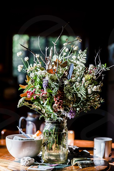 dry flower bouquet in a glass jar on a table with mugs and white bowl photo