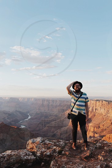 smiling man in white blue green and yellow striped button up t-shirt and black pants wearing eyeglasses with black sling bag standing on canyon under blue and white sunny cloudy sky photo