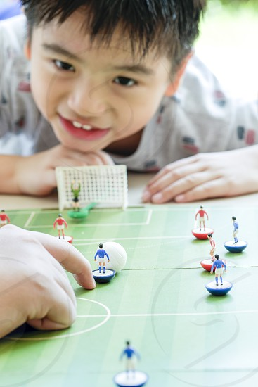 Close-up of a happy kid playing table soccer. Shallow depth of field. Focus on foreground. photo