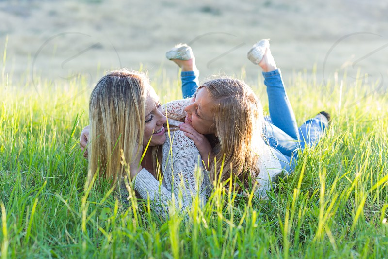 mother and daughter cuddling on green grass during daytime photo