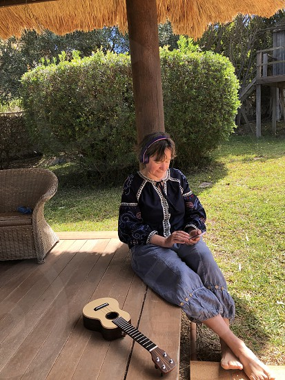 Woman with headphones on checking her mobile phone with a ukulele beside her sitting on the floor of a wooden hut in the garden photo