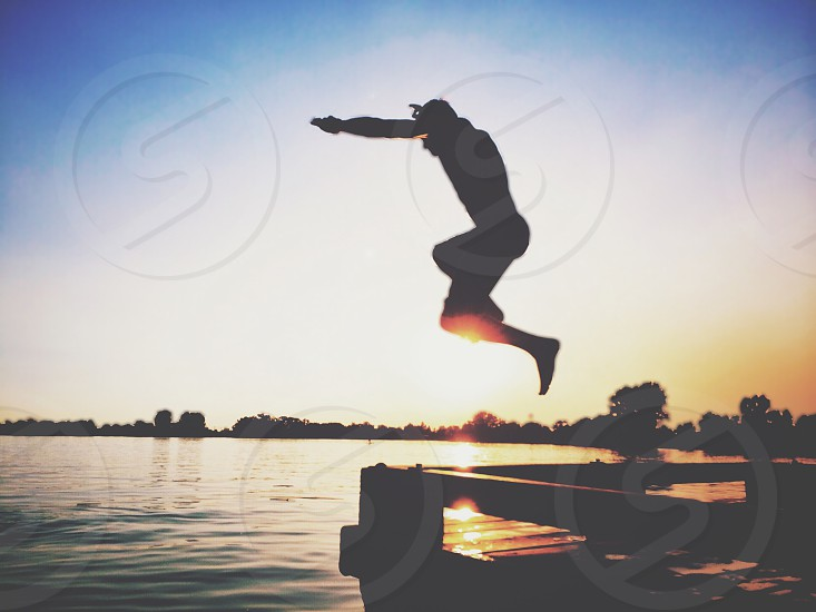 man man jump off dock photo