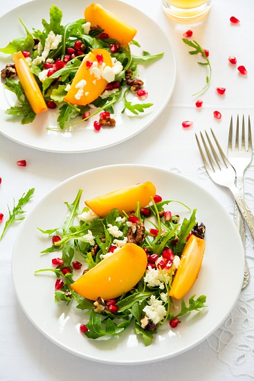 Fresh autumn salad with persimmon arugula cheese and pomegranate seeds on white table cloth. Space for copy photo