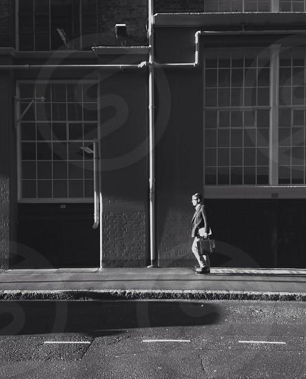 man walking by concrete building photo