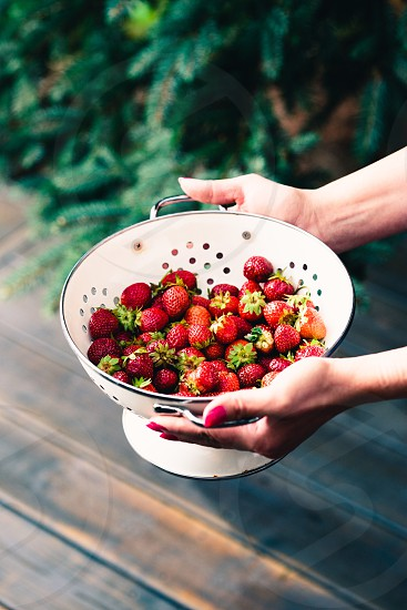 Female hand holding bowl of fresh strawberries sprinkled raindrops over wooden table photo