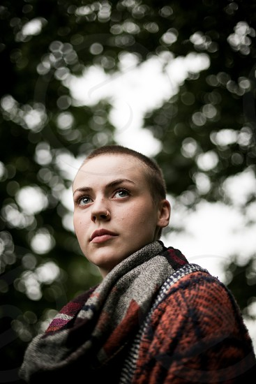 Bald or short haired young woman with nose piercing and alternative clothing with some nice bokeh in a natural setting photo