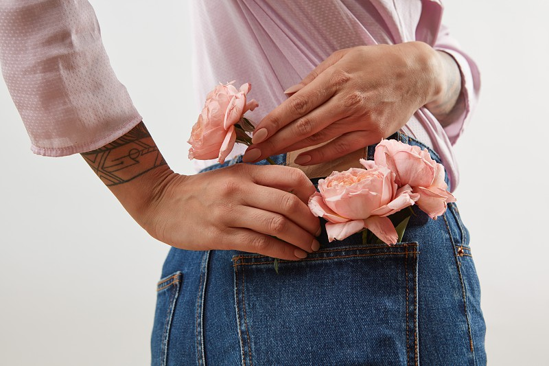 Young girl wearing of jeans pants and pink shirt from back put in natural flowers roses in a pocket on a gray background place for text. Concept of Woman's or Mother's Day. photo