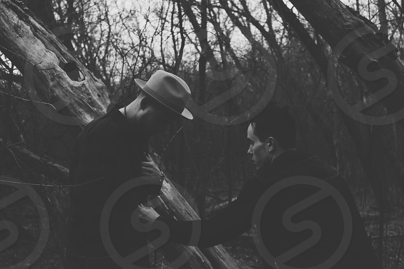 gray scale photography of two person on the forest near leafless tress during daytime photo