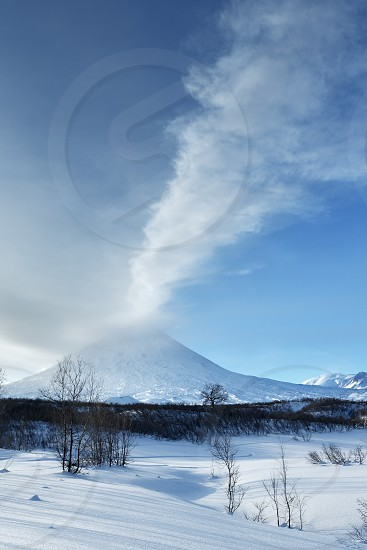 Beauty winterly landscape of Kamchatka: evening view of eruption active Klyuchevskoy Volcano (Klyuchevskaya Sopka) - eructation from crater of volcano plume of gas steam and ashes. Eurasia Far East Russia Kamchatsky Krai. photo