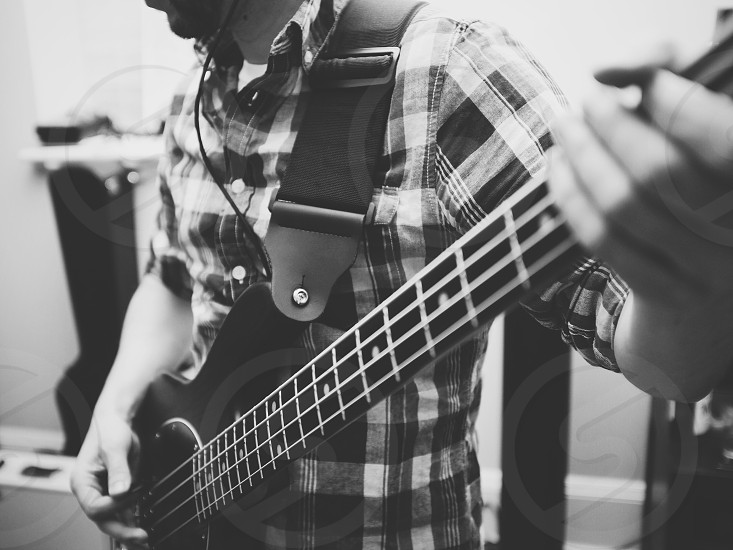 man playing electric bass guitar black and white photo photo