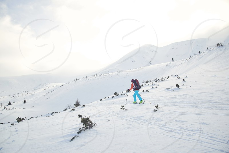 Ski touring hiking up a summit in mountains photo