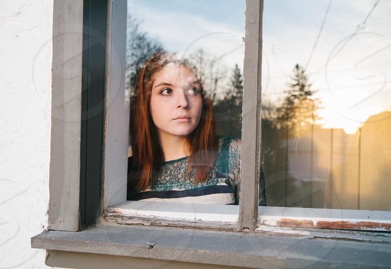 woman on window looking up photo