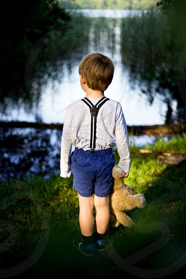 toddler wearing blue romper shorts holding bear plush toy standing near body of water photo