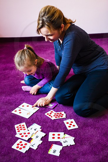 Mother teaching counting her little daughter using card game sitting on a carpet at home photo