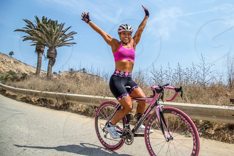 Fit woman riding bike with arms in the air photo