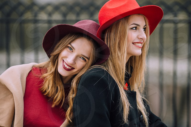 two smiling women wearing red hats red tops and one wearing a brown jacket and the other in a black jacket photo