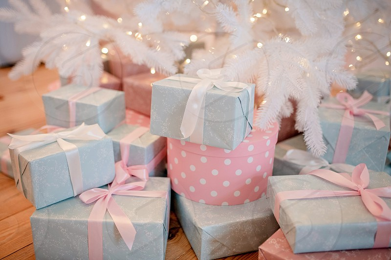many beautifully wrapped gifts with ribbons under the holiday tree. Merry Christmas and Happy New Year surprise for children from Santa Claus. photo