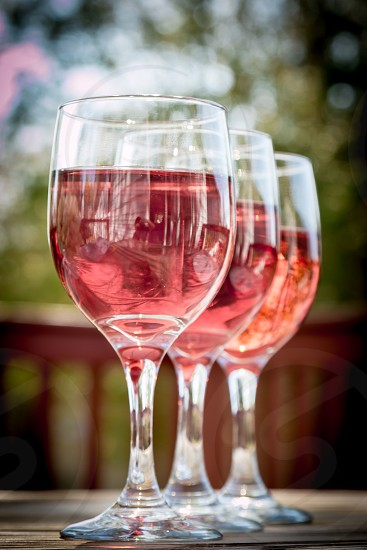 3 wine glass with red wine line up on the table photo