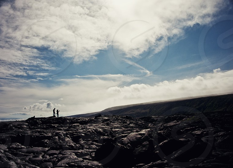 A couple silhouetted in the harsh daylight sun on the lava fields at the Kilauea Volcano Hawaii.  photo