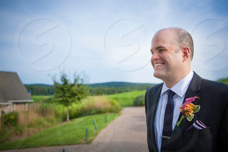 man in black formal suit with orange flower corsage photo